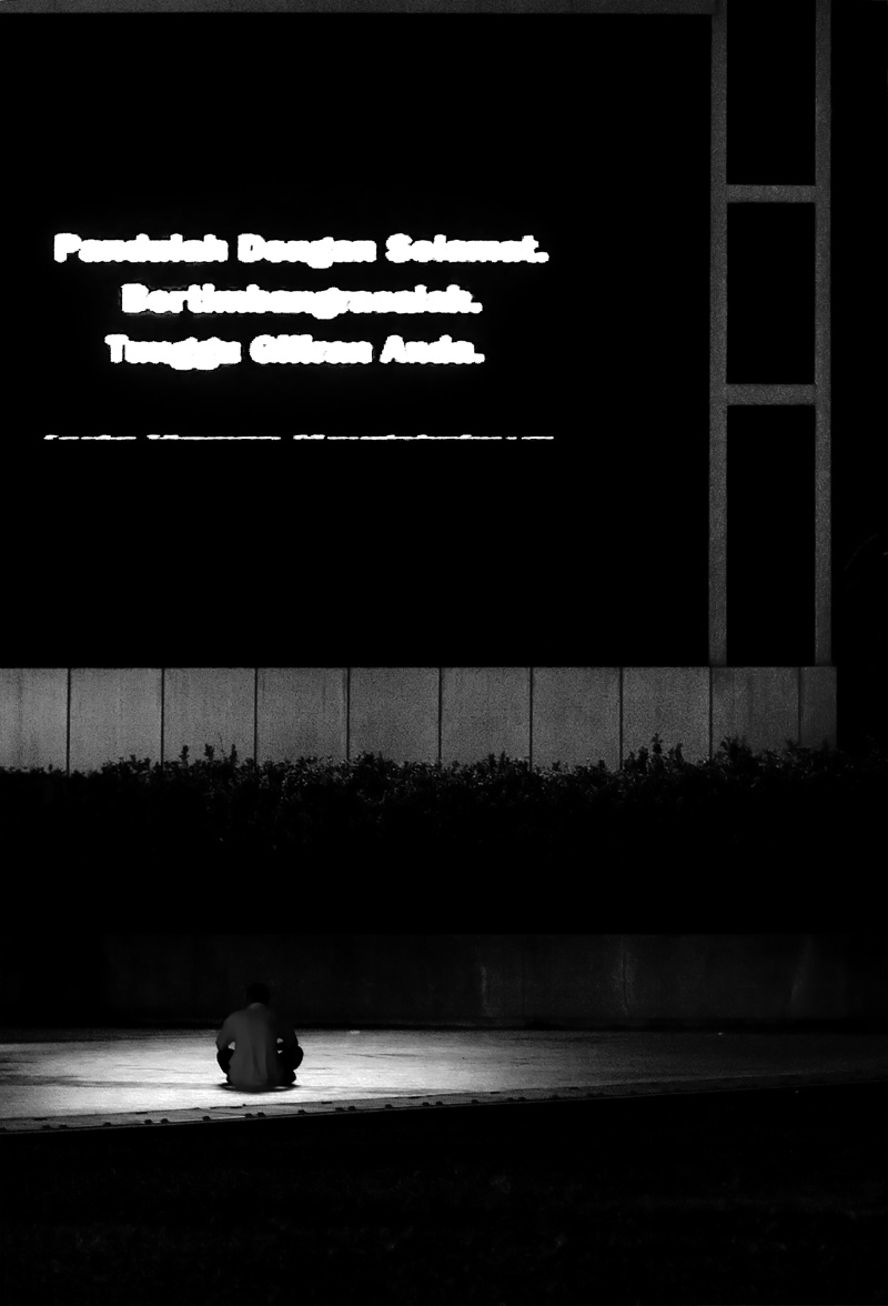 A man watches a giant screen television on a downtown sidewalk. - Kuala Lumpur, Malaysia - Daily Travel Photos