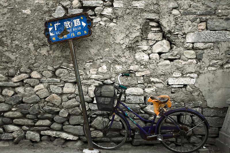 A bicycle parked against a wall. - Dali, Yunnan, China - Daily Travel Photos