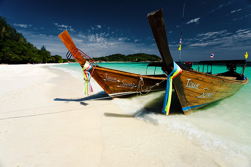 Longtail boats wait on a beautiful white sand beach on Pattaya beach on Ko Lipe. - Lipeh, Satun, Thailand - Daily Travel Photos