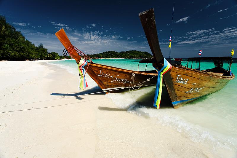Longtail boats wait on a beautiful white sand beach on Pattaya beach on Ko Lipe. - Lipeh, Satun, Thailand - Daily Travel Photos