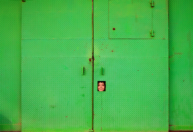 A playful child peeks out of a hole in a metal gate. - Makassar, Sulawesi, Indonesia - Daily Travel Photos