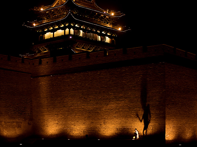 A Chinese child plays in the spotlights creating a large shadow against the city wall. - Pingyao, Shanxi, China - Daily Travel Photos