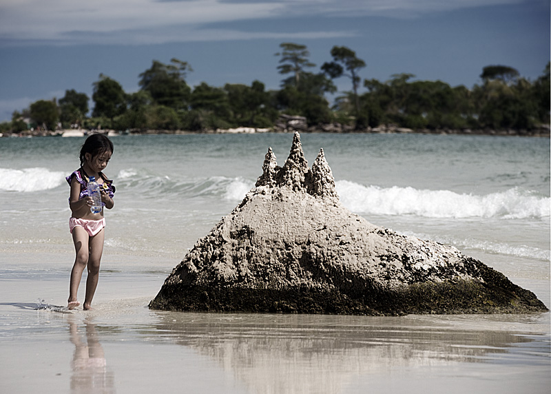 A young girl builds a sandcastle on a beach. - Sihanoukville, Cambodia - Daily Travel Photos