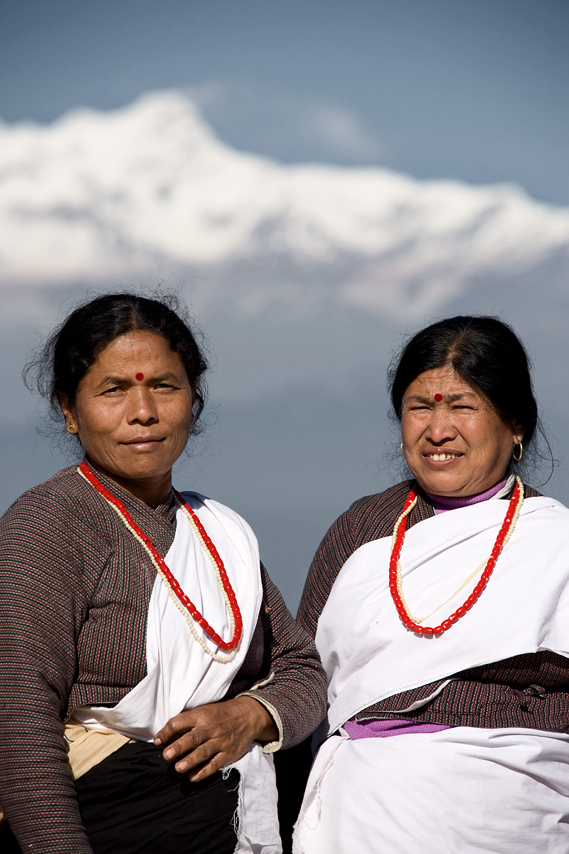 Two tribal women in colorful traditional clothes backed by the Himalayan mountains. - Bandipur, Nepal - Daily Travel Photos