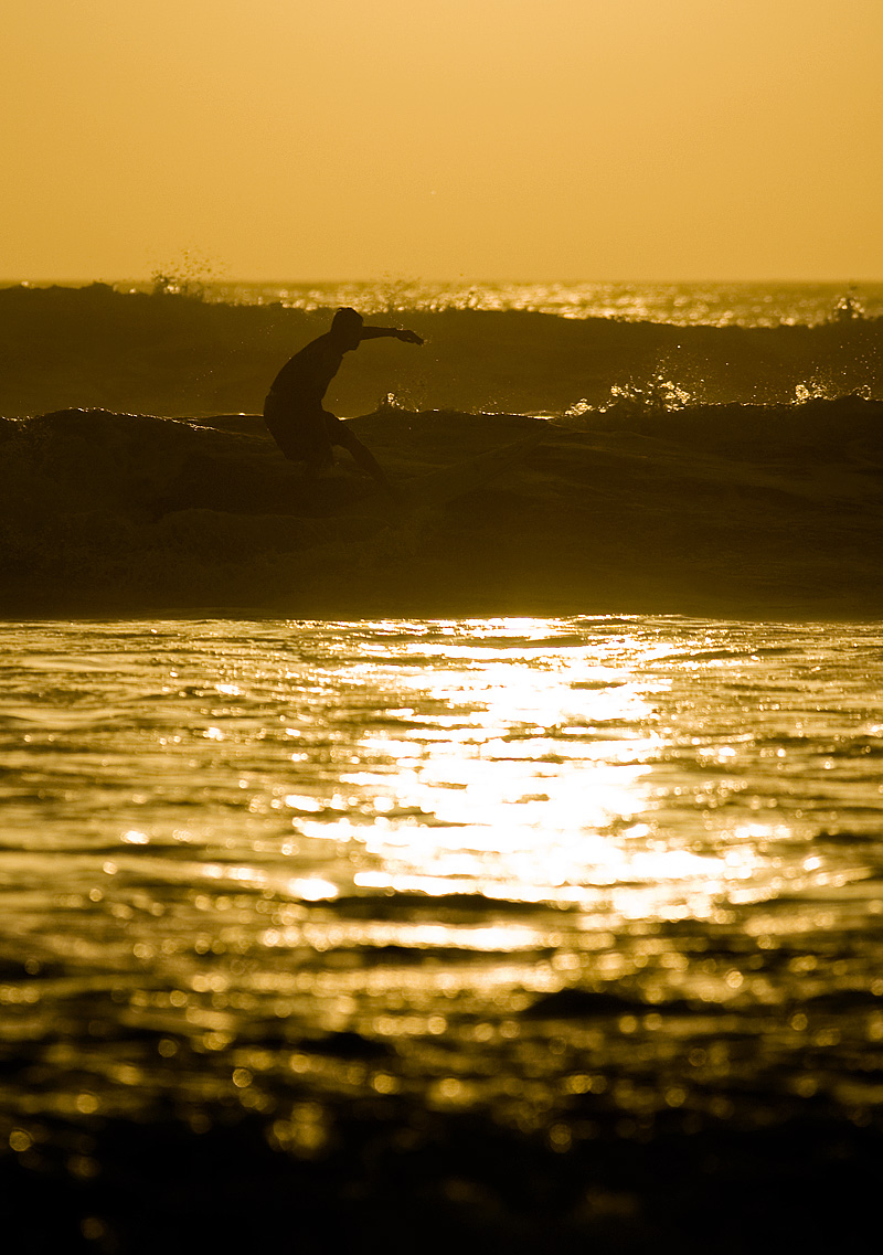 A surfer at sunset rides a wave. - Kuta, Bali, Indonesia  - Daily Travel Photos