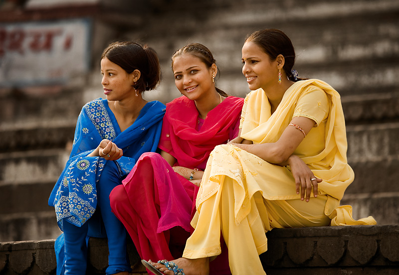 Three beautiful young Indian girls sit in colorful clothes on the ghats along the Ganges river. - Varanasi, Uttar Pradesh, India - Daily Travel Photos