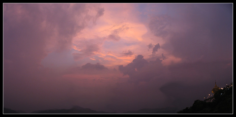 The holy Golden Boulder stands against a pink sunset sky. - Kyaiktiyo, Myanmar - Daily Travel Photos