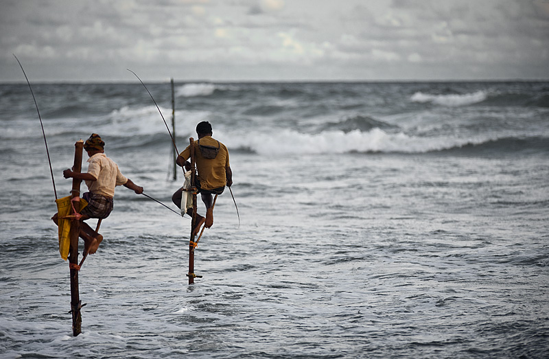 Stilt fishermen fish over a rough ocean. - Hikkaduwa, Sri Lanka - Daily Travel Photos