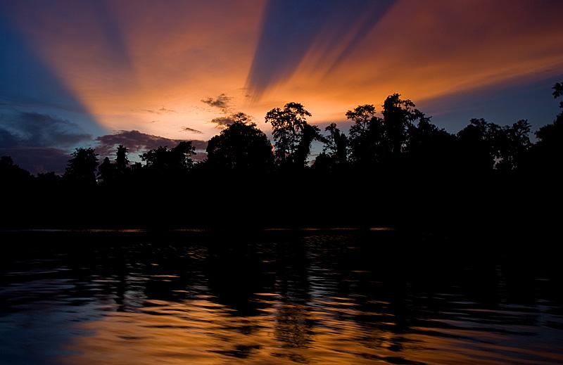 A beautiful sunset casts strange shadows in the sky. - Sungei Kinabatangan, Sabah, Borneo, Malaysia - Daily Travel Photos
