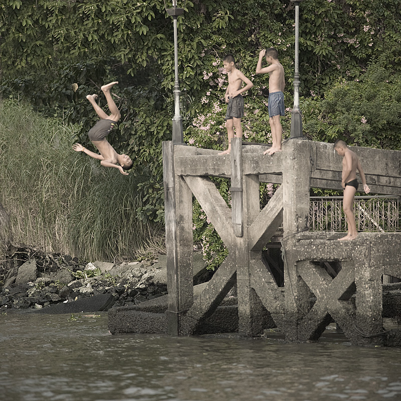 Thai children jump into the Chao Phraya river from a raised pier. - Bangkok, Thailand - Daily Travel Photos