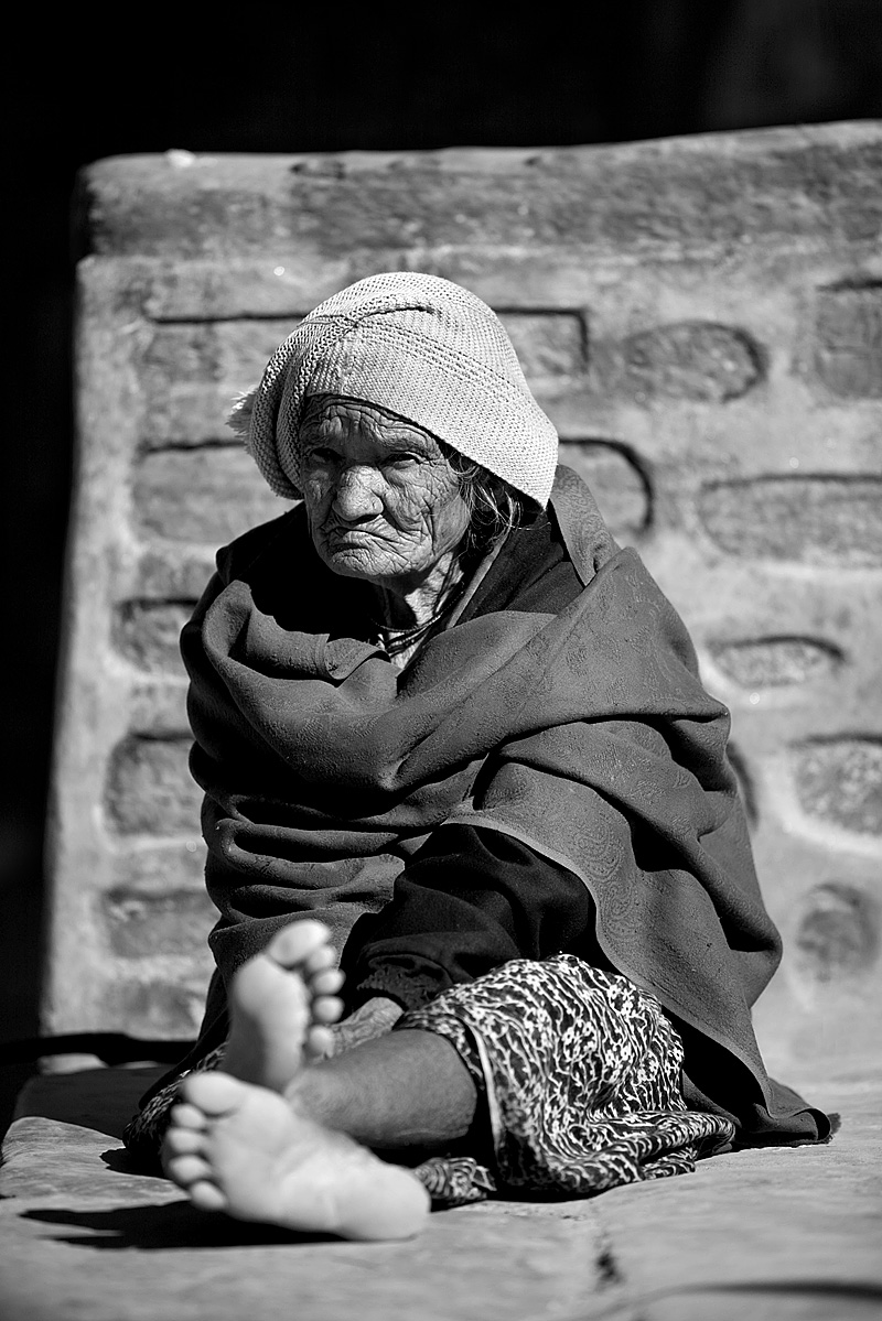 An aged Nepali woman sits on a stone slab. - Bandipur, Nepal - Daily Travel Photos