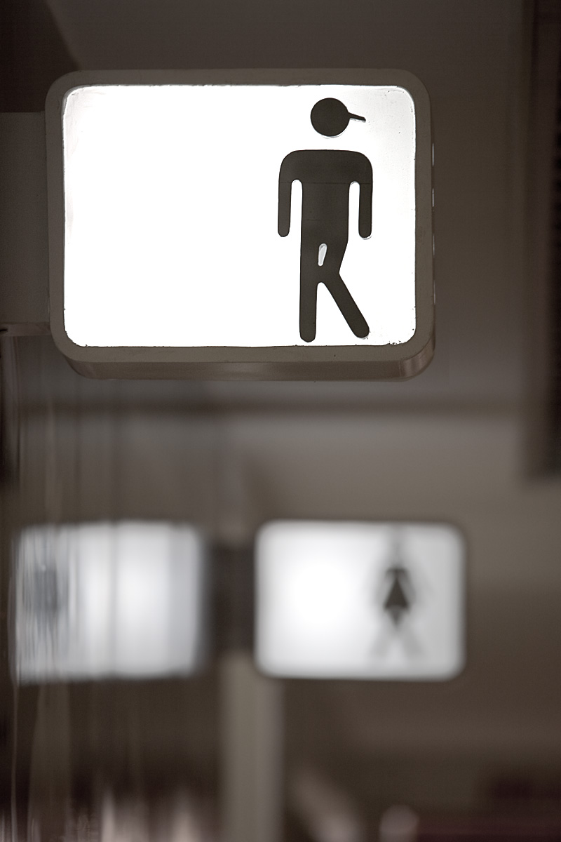 A humorous public bathroom sign displaying an impatient stick figure with knees crossed. - Bangkok, Thailand - Daily Travel Photos