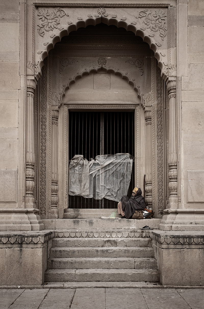 A homeless Indian man occupies the steps of a mansion on the Ganges river. - Varanasi, Uttar Pradesh, India - Daily Travel Photos