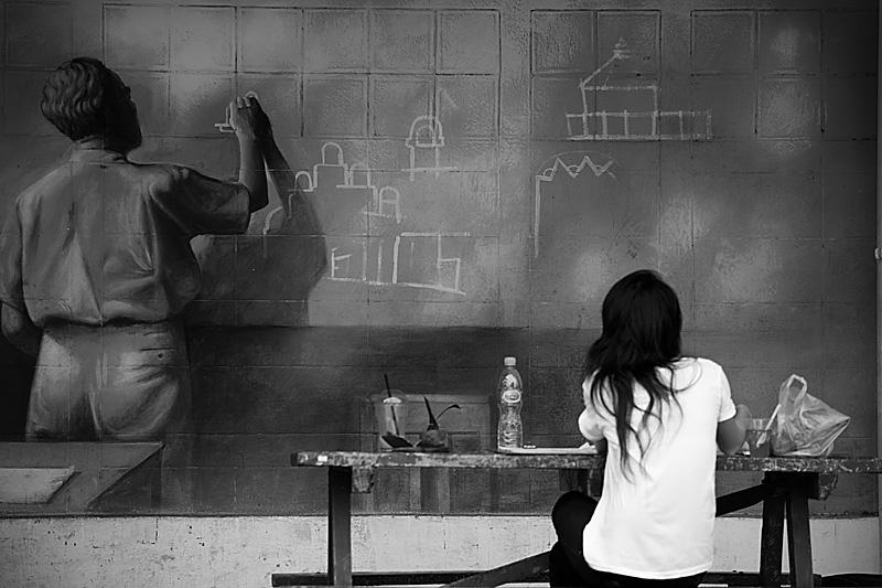 A young Thai student stares at wall art.  - Bangkok, Thailand - Daily Travel Photos