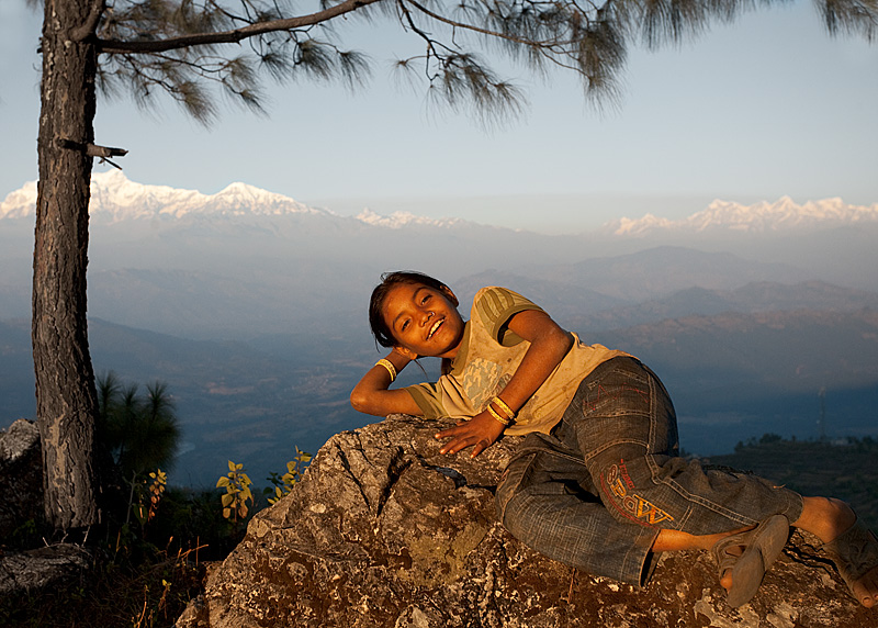 A cute Nepali girl poses with a Himalayan mountain background. - Bandipur, Nepal - Daily Travel Photos