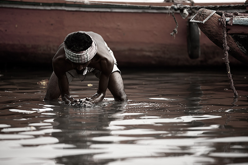 An Indian man dredges in the Ganges river for loose change.  - Varanasi, Uttar Pradesh, India - Daily Travel Photos