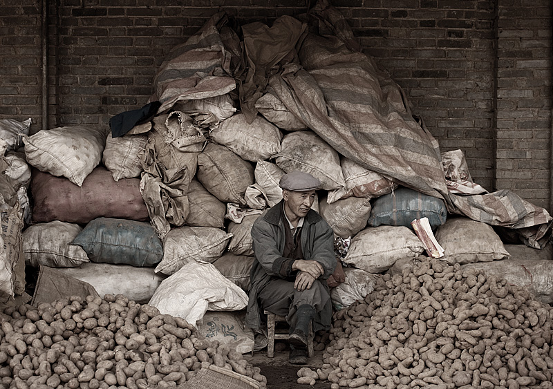 A Chinese salesman sits on his stash of potatoes. - Lijiang, Yunan, China - Daily Travel Photos