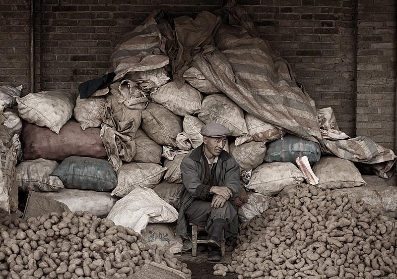 A Chinese salesman sits on his stash of potatoes. - Lijiang, Yunan, China - Daily Travel Photos