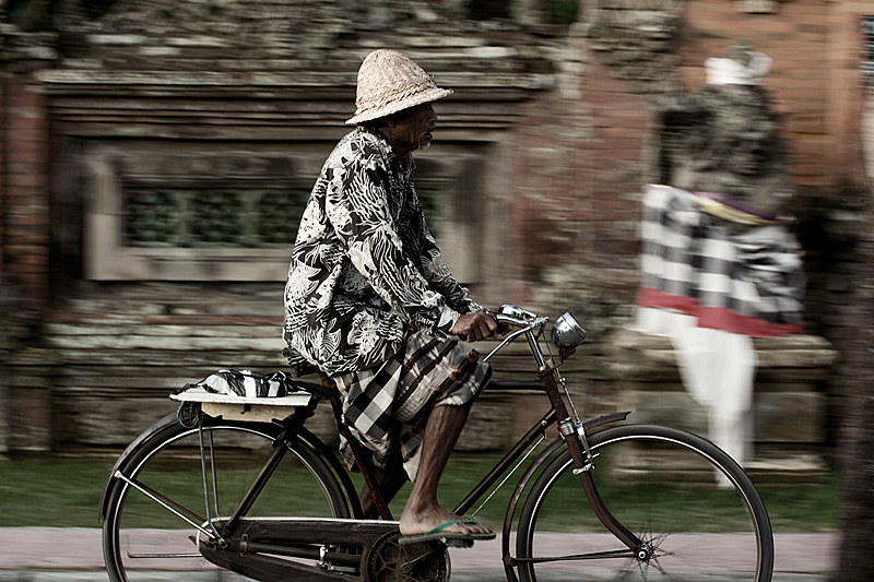 A motion blur of a Balinese man riding a bicycle. - Ubud, Bali, Indonesia - Daily Travel Photos