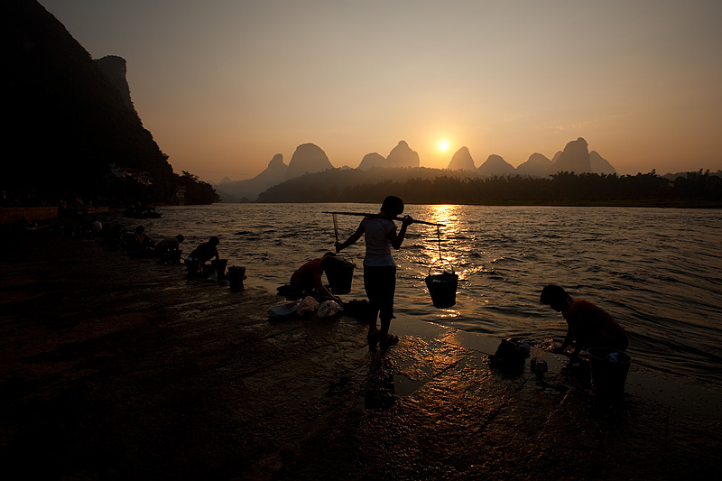 Karsts formations and women doing laundry on the river. - Yangshuo, Guanxi, China - Daily Travel Photos