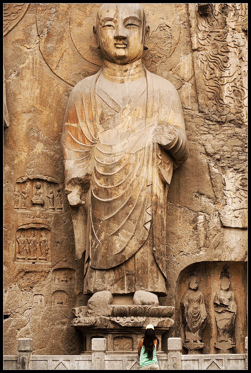 A Chinese girl admires Buddhist carvings at UNESCO site, Luoyang. - Luoyang, Henan, China - Daily Travel Photos