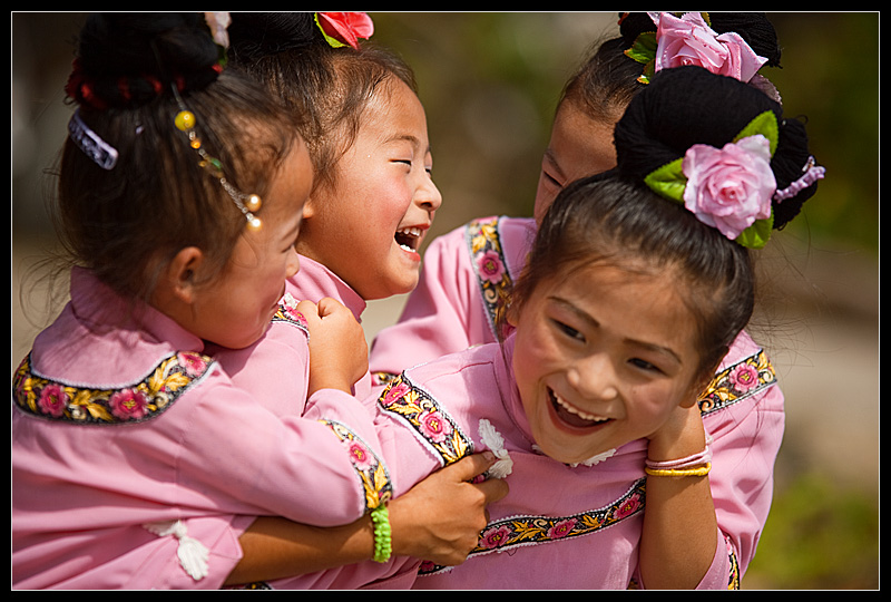 Young cute Miao minority girls play before a performance during a festival. - Xijiang, Guizhou, China - Daily Travel Photos