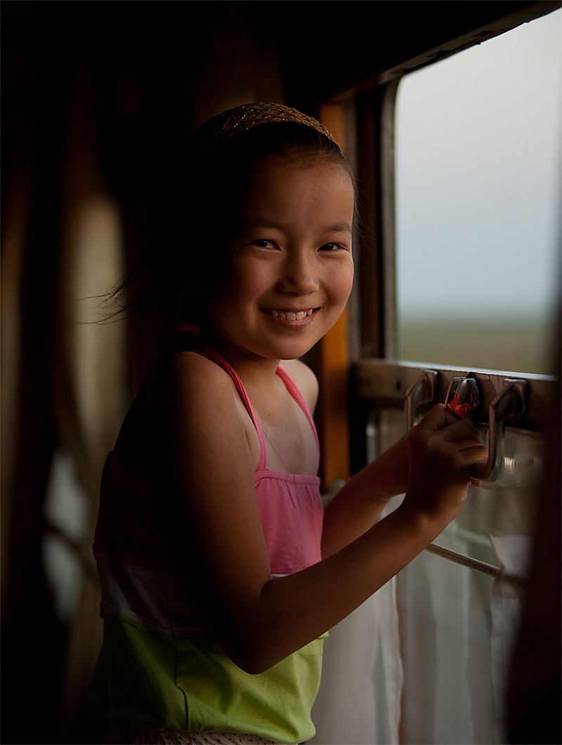 A cute young Mongolian girl looks out the window of a train. - Ulaan Baatar, Mongolia - Daily Travel Photos