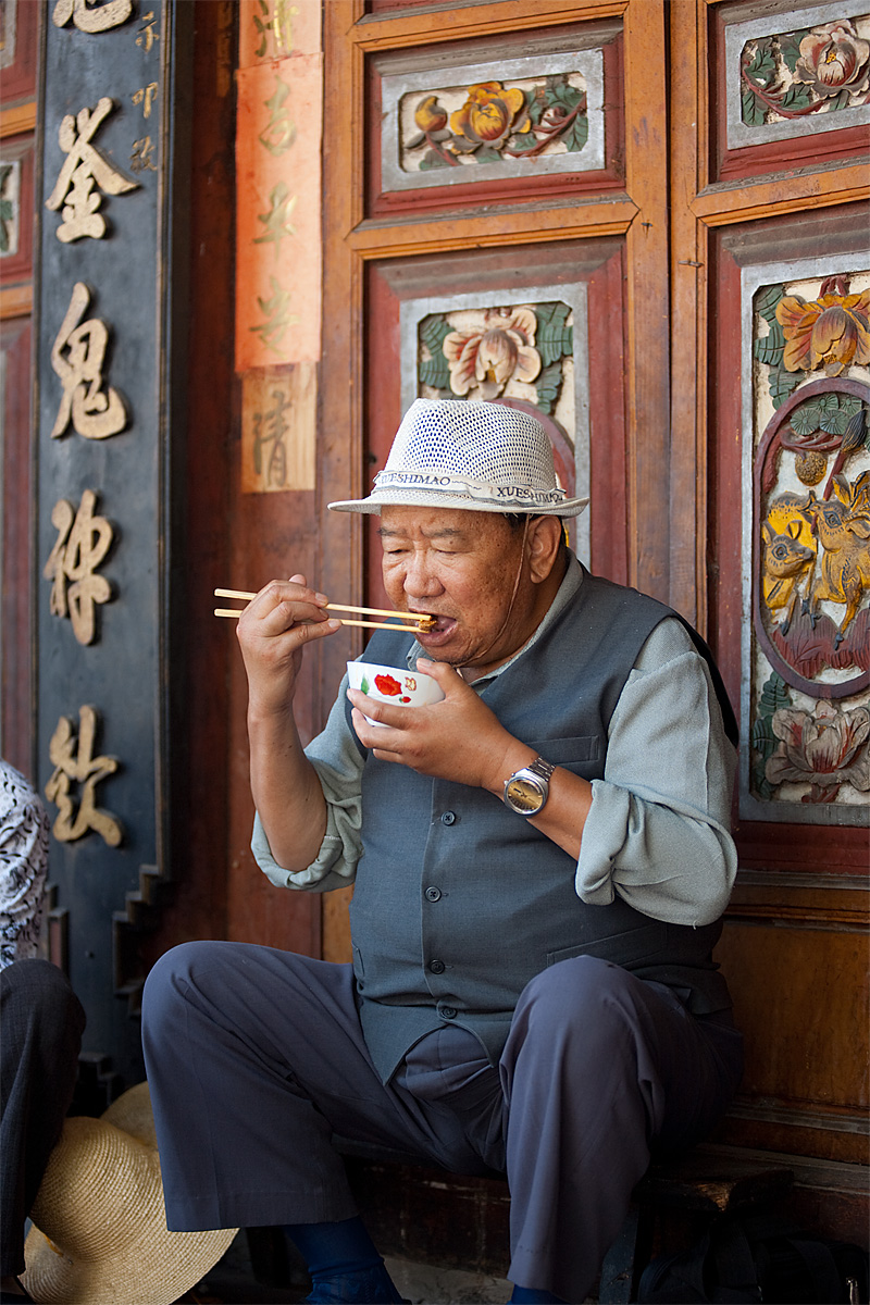 A Chinese man concentrating on his food and chopsticks. - Dali, Yunnan, China - Daily Travel Photos