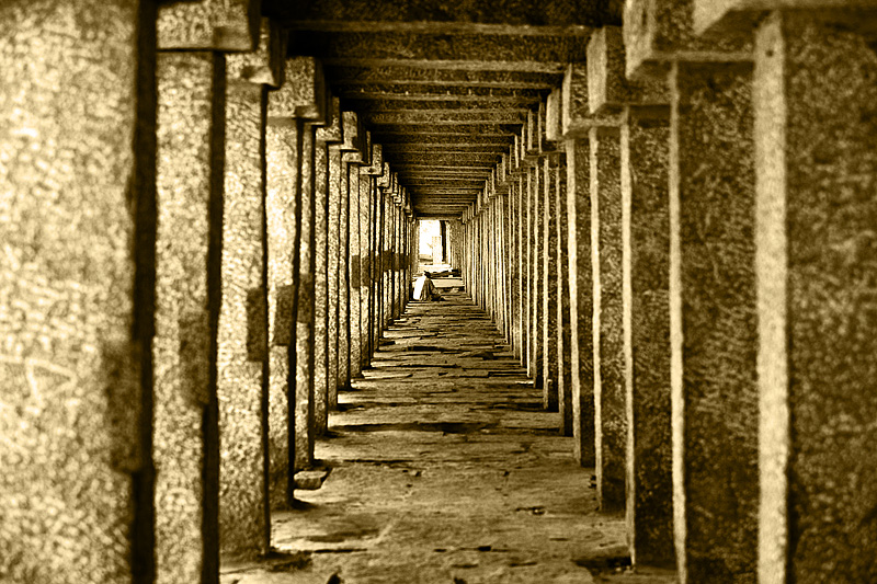 A man rests at the end of a series of pillars. - Hampi, Karnataka, India - Daily Travel Photos