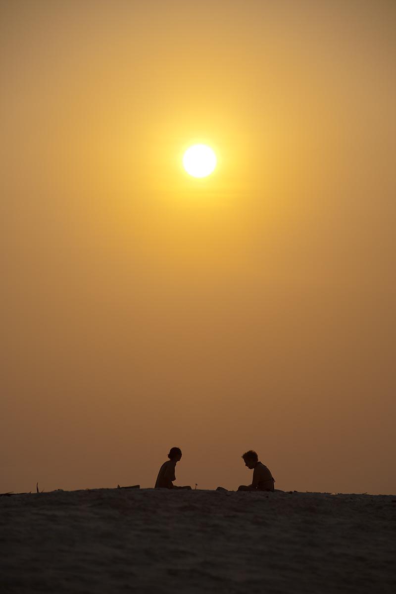 Women sunbathe topless at sunset beach. - Koh Lipeh, Thailand - Daily Travel Photos
