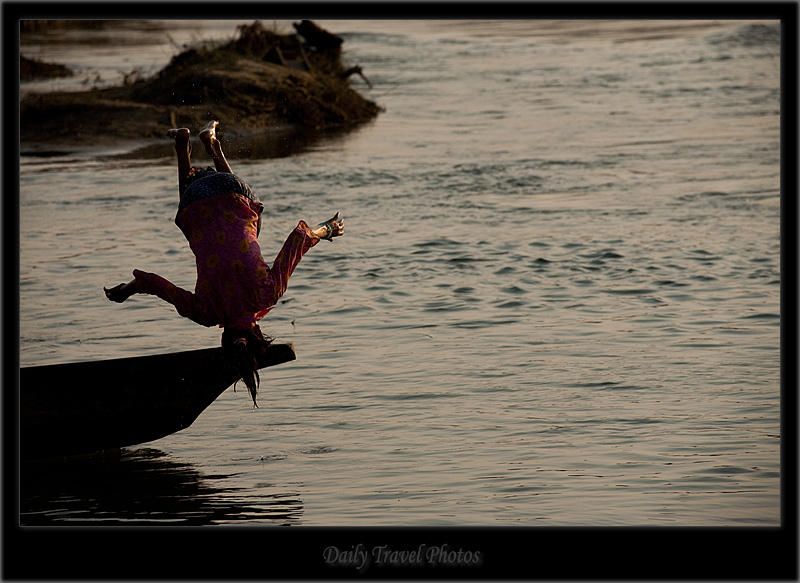 A young girl jumps from a boat - Chitwan, Nepal - Daily Travel Photos