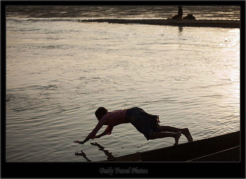 A young girl dives from a boat - Chitwan, Nepal - Daily Travel Photos