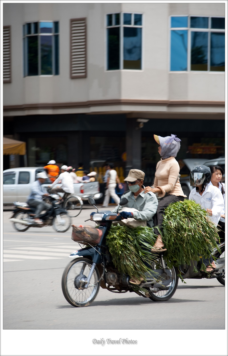 A woman rides motorcycle pillion on a stack of produce - Phnom Penh, Cambodia - Daily Travel Photos