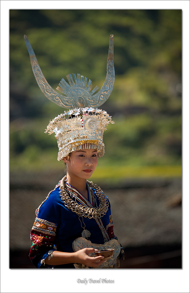 A traditionally dressed and ornately decorated Miao ethnic minority girl waits for a festival - Xijiang, Guizhou, China - Daily Travel Photos
