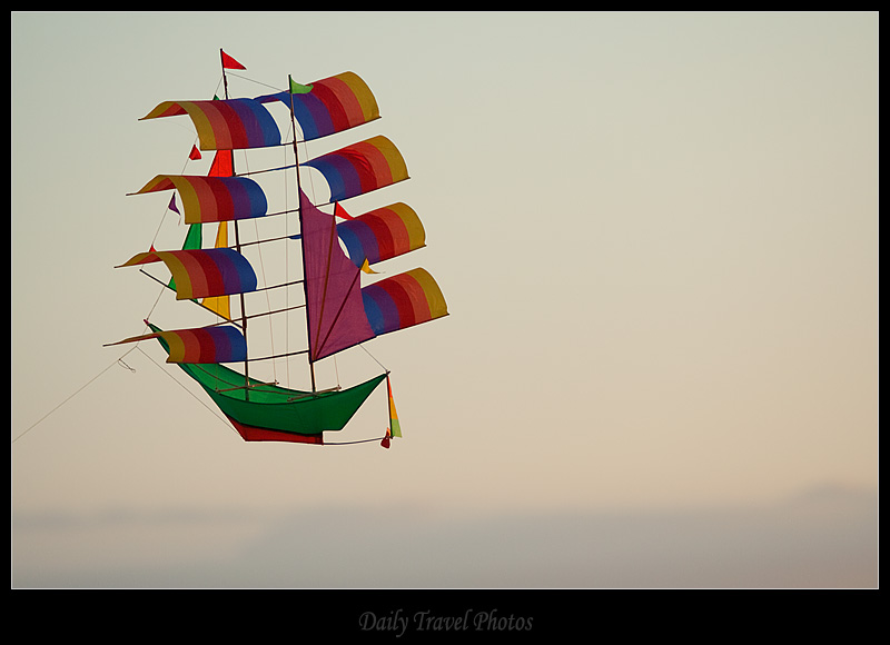 A sailboat kite flies in a blue sky - Kuta, Bali, Indonesia - Daily Travel Photos