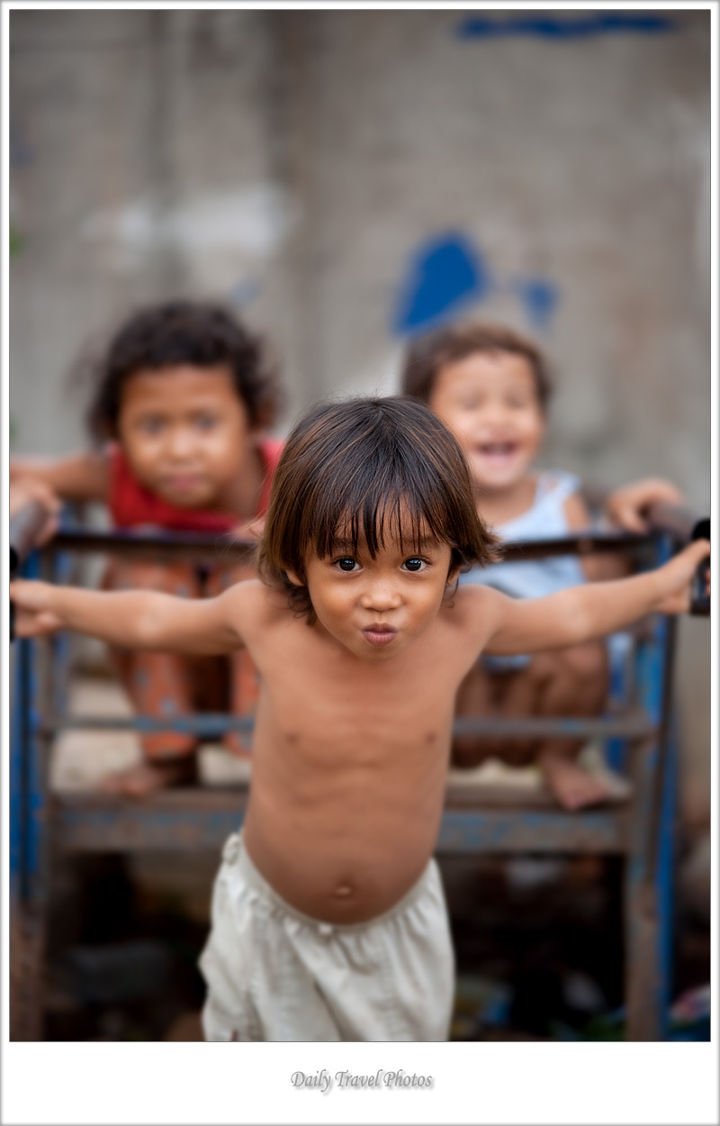 Cute young Cambodian boy pulls his friends in a cart - Kompong Thom, Cambodia - Daily Travel Photos
