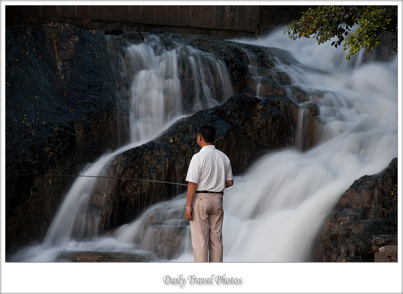 A Chinese man fishing in a small flowing stream - Yangshuo, Guanxi, China - Daily Travel Photos