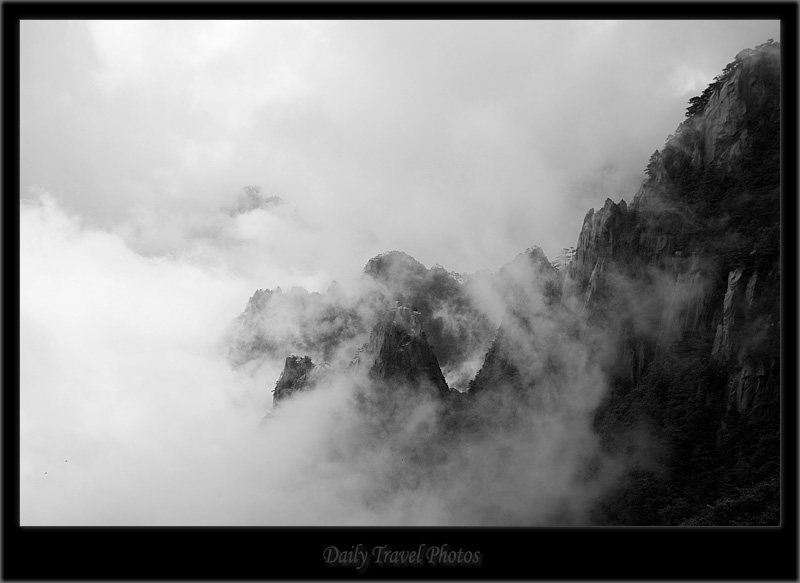 Misty peaks of a mountain range poke through - Huangshan, Zhejiang, China - Daily Travel Photos