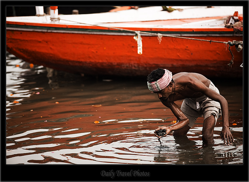 An Indian man looks at his find in the Ganges river - Varanasi, Uttar Pradesh, India - Daily Travel Photos