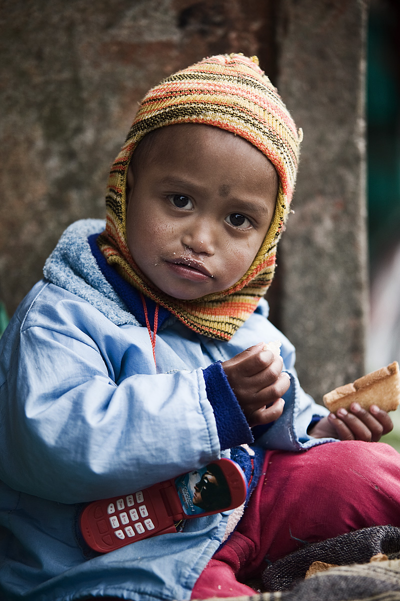 Cute Indian Kid Winter Hat Eating Bread - Darjeeling, West Bengal, India - Daily Travel Photos
