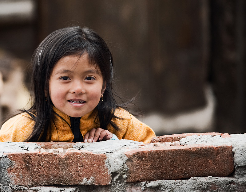 Cute Nepali Girl Brick Wall Smiling - Darjeeling, West Bengal, India - Daily Travel Photos