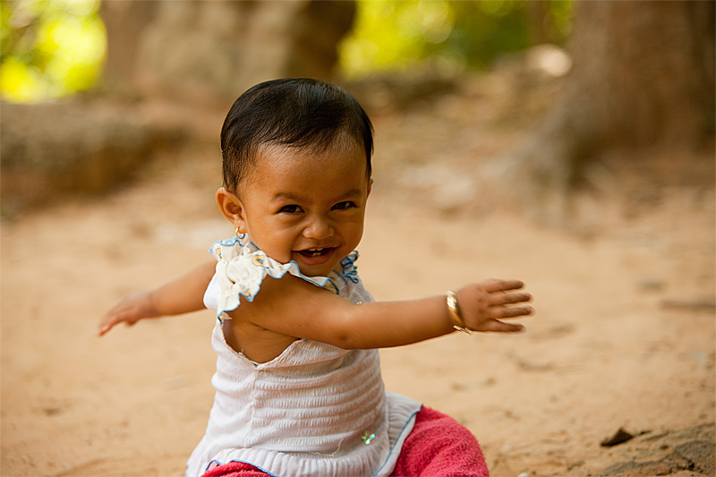 Baby Twisting Ground Eye Contact Angkor Wat Cutest In The World- Siem Reap, Cambodia - Daily Travel Photos