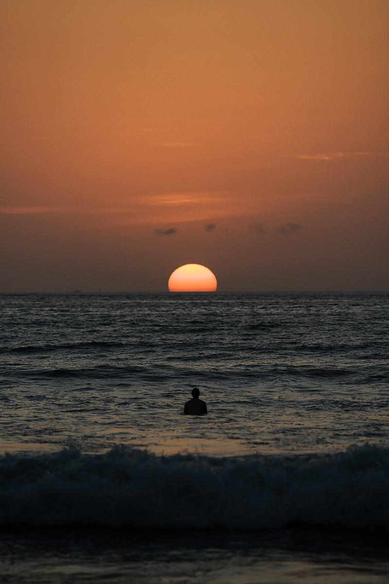 Surfer Waiting Wave Sun Dips Ocean - Kuta, Bali, Indonesia - Daily Travel Photos