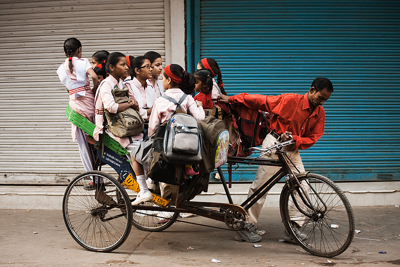 many children sit inside a cycle rickshaw ready for school - Delhi, India - Daily Travel Photos