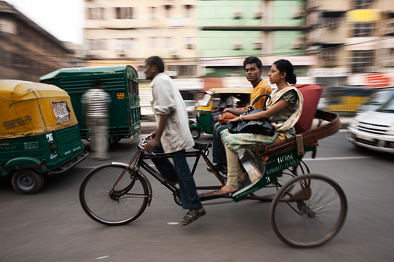 Panning shot of a cycle rickshaw and passengers in a downtown street - Delhi, India - Daily Travel Photos