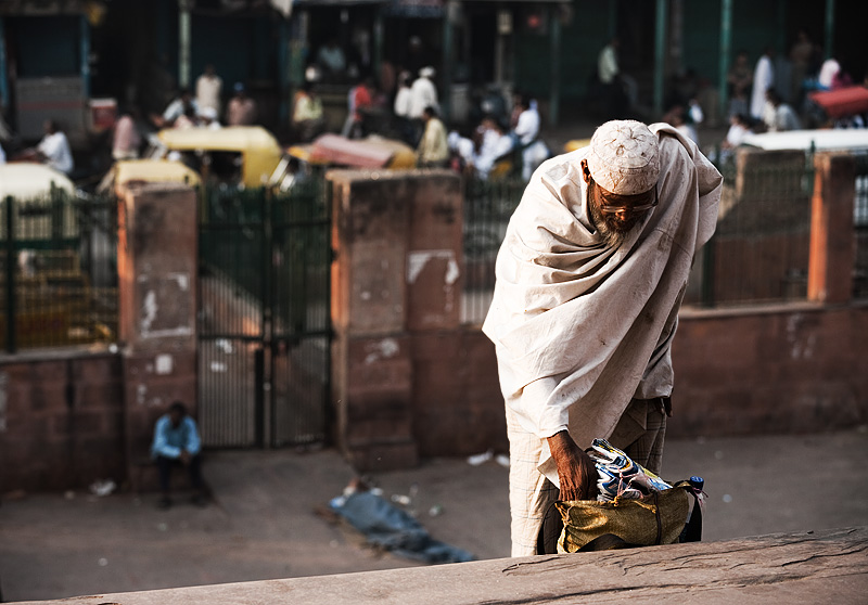 A Muslim beggar sifts through his bag on the steps of Jama Masjid. - Delhi, India - Daily Travel Photos