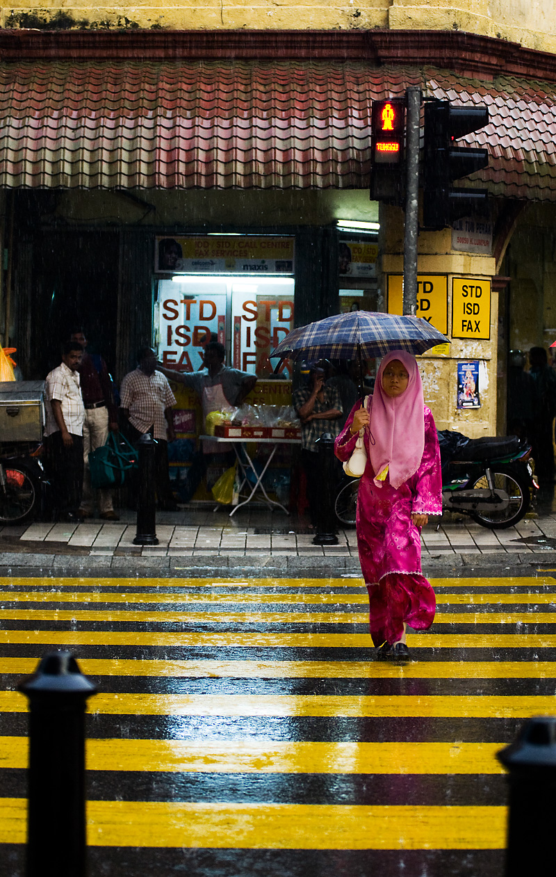 A Malaysian woman dressed in red clothes and pink head scarf crosses a striped street in the rain covered by a plaid umbrella. - Kuala Lumpur, Malaysia - Daily Travel Photos