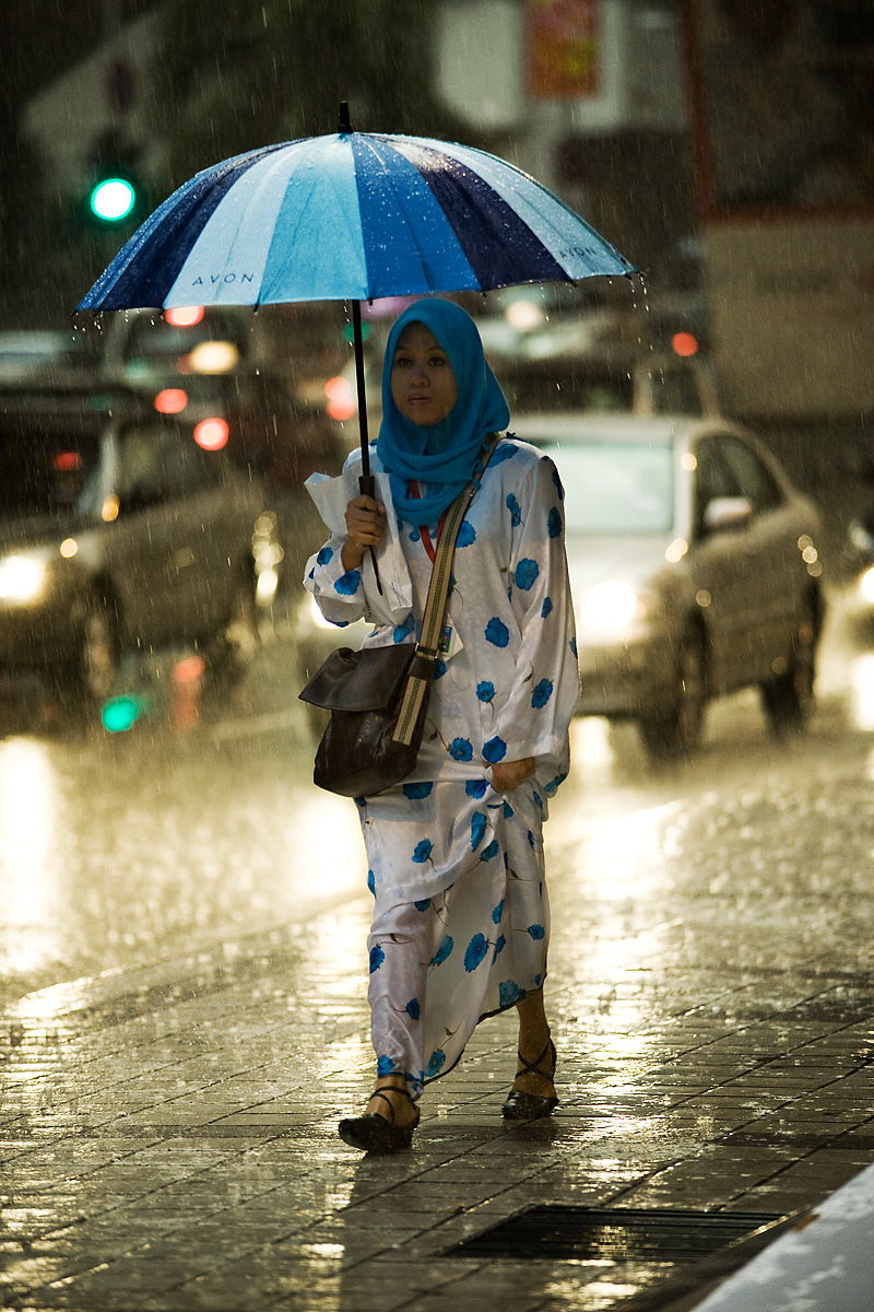 A Malaysian woman in blue Muslim dress and head scarf walks in the rain covered by a matching blue umbrella. - Kuala Lumpur, Malaysia - Daily Travel Photos