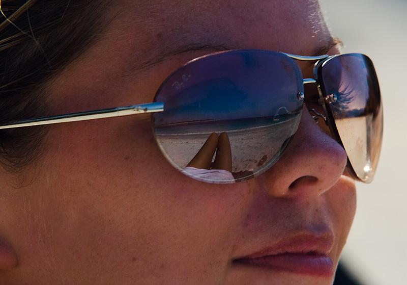 A beautiful British woman's sunglasses reflect the multi-colored sea before her.  - Gili Tranwangan, Lombok, Indonesia - Daily Travel Photos