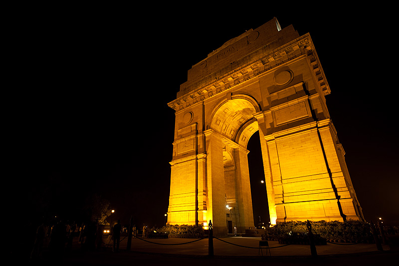 India Gate, memorial for fallen Indian soldiers lighted at night with the rising moon through its legs. - Delhi, India - Daily Travel Photos